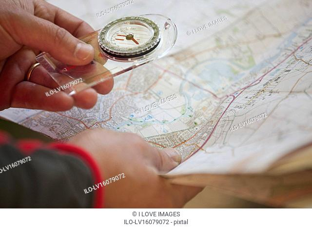 A man holding a map and compass, close up
