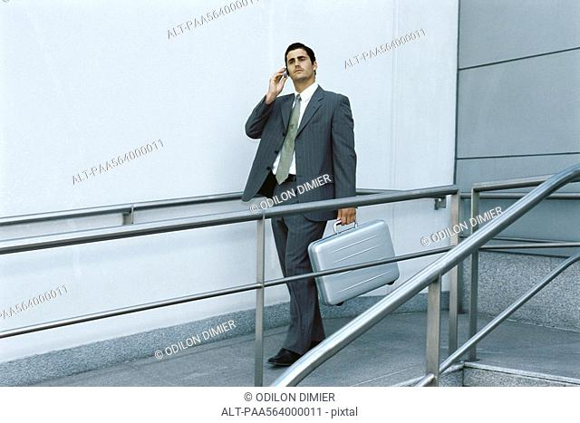 Businessman walking on sidewalk using cell phone, carrying briefcase