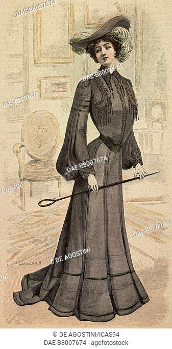 Woman wearing a dark grey Drap visiting dress, corset with wide sleeves, velours belt and a felt hat with ostrich feathers, creation by Mademoiselle Goery
