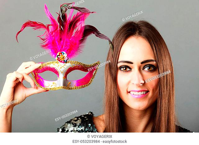 Holidays, people and celebration concept. Closeup woman holding pink carnival venetian mask in hand on gray background