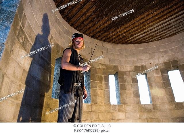 Portrait of a pirate armed with a sword inside a castle turret