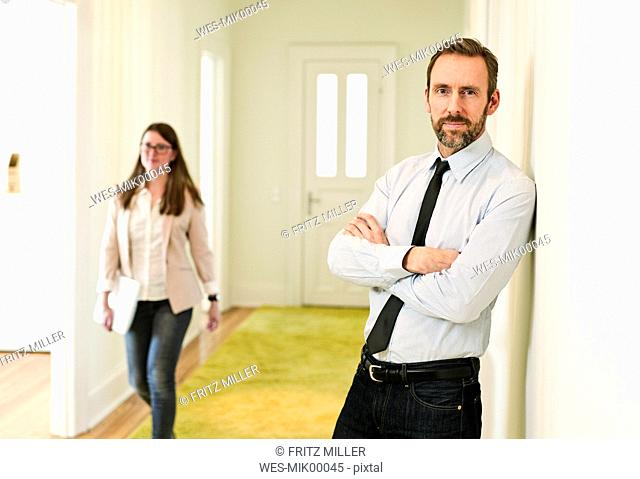 Portrait of businessman leaning against the wall on office floor