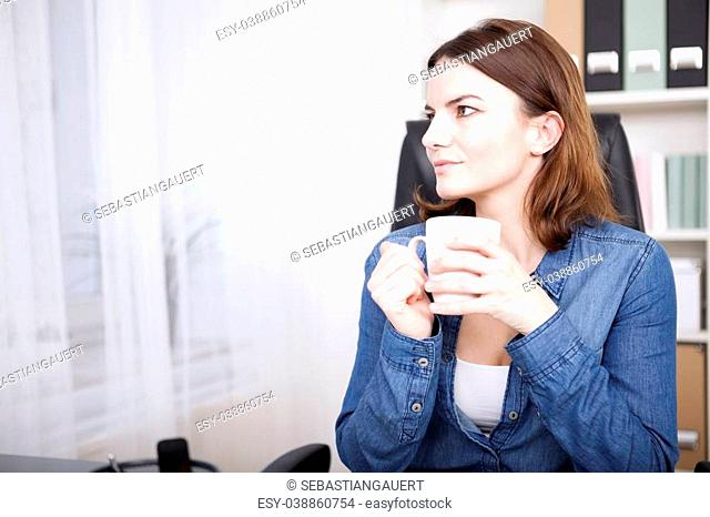 Businesswoman sitting thinking at her desk as she enjoys a coffee break staring off to the side with a quiet smile, with copyspace