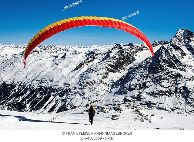 Paraglider taking off, Corvatsch Glacier in winter, Bernina range at back, St. Moritz, Engadin, Switzerland