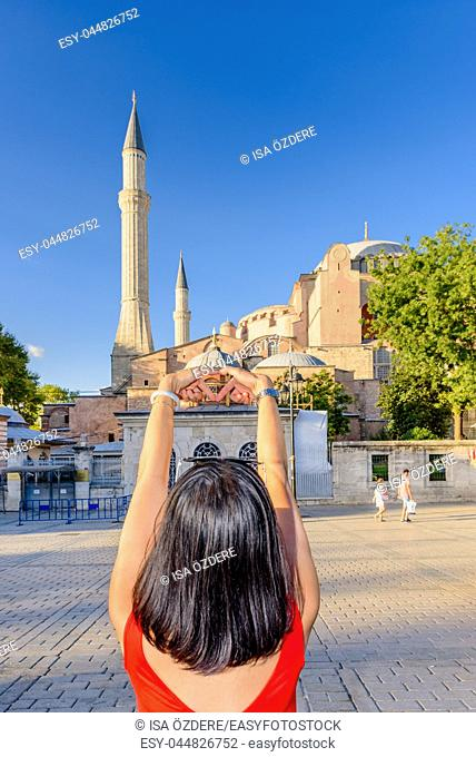 Beautiful woman makes heart shape with view of Hagia Sophia on background in Istanbul,Turkey