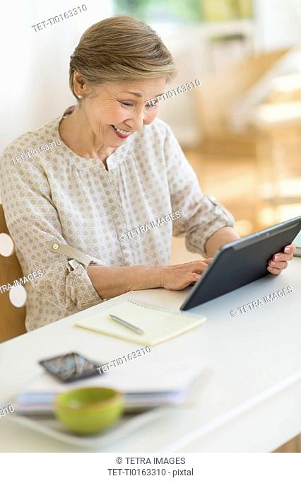 Senior woman using tablet pc at home