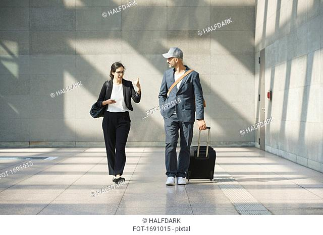 Male and female business colleagues talking while walking at airport
