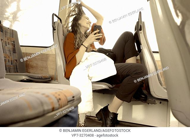 young woman sitting in public transport with phone, playing with hairs, in city Cottbus, Brandenburg, Germany