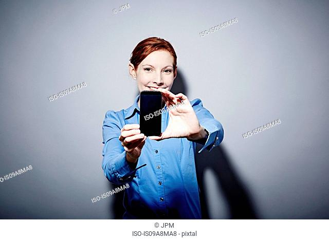 Studio portrait of young woman holding up camera phone