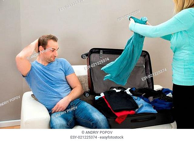 Man Sitting Beside The Suitcase While Woman Folding Clothes