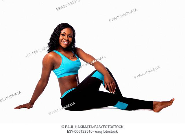 Beautiful happy woman doing floor workout fitness exercise for health with legs crossed, bodycare concept