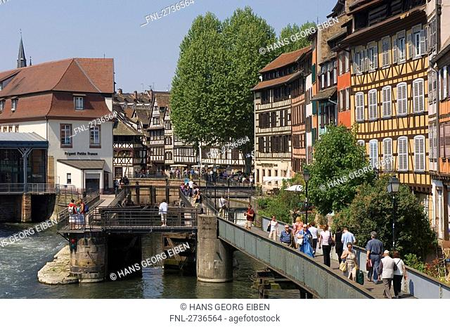 People walking on bridge in front of timber framed houses, Strasbourg, Germany