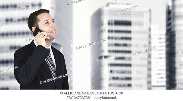 Businessman Talking On The Phone With Business City and Corporate Buildings In Background