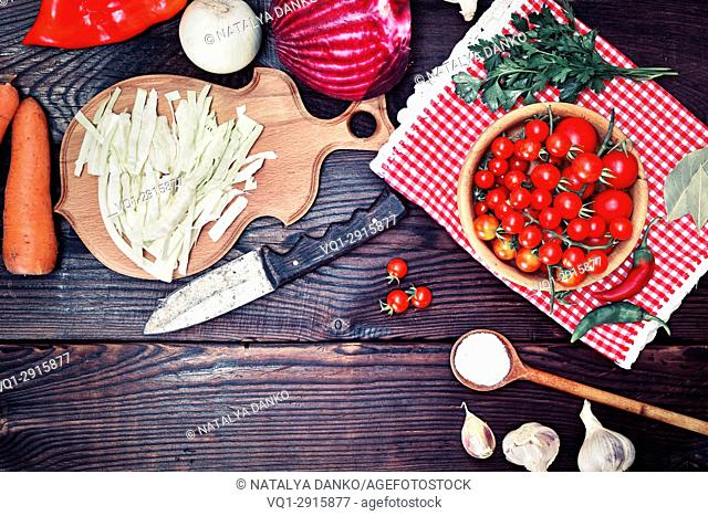 Fresh vegetables for cooking traditional Ukrainian soup borscht on a brown wooden background, top view