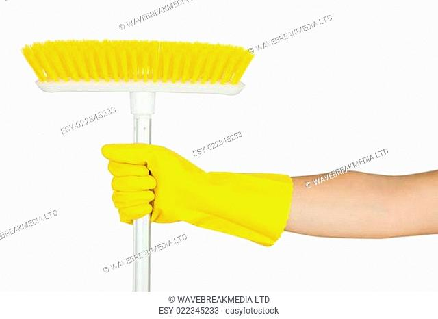 Hand in rubber glove holding sweeping brush