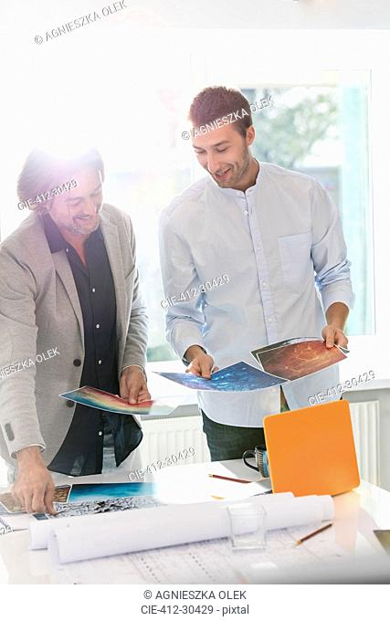Creative businessmen reviewing photography proofs in office