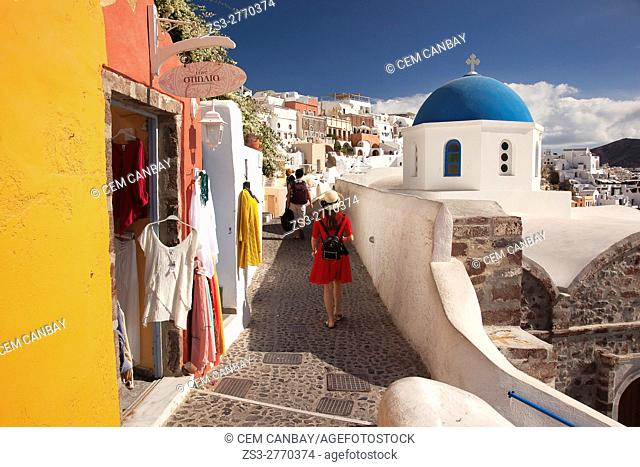 Blue domed church and people walking in the alleys of the Oia village, Santorini, Cyclades Islands, Greek Islands, Greece, Europe