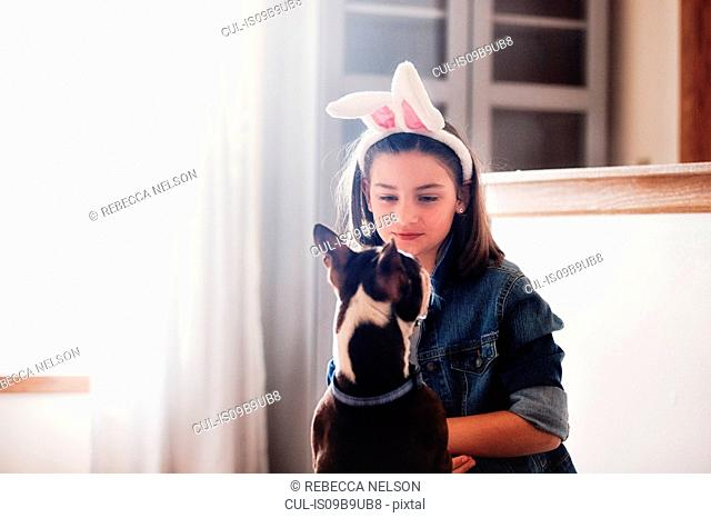 Girl sitting with dog, indoors, girl wearing Easter bunny ears