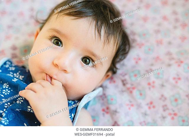 Portrait of baby girl with finger in mouth