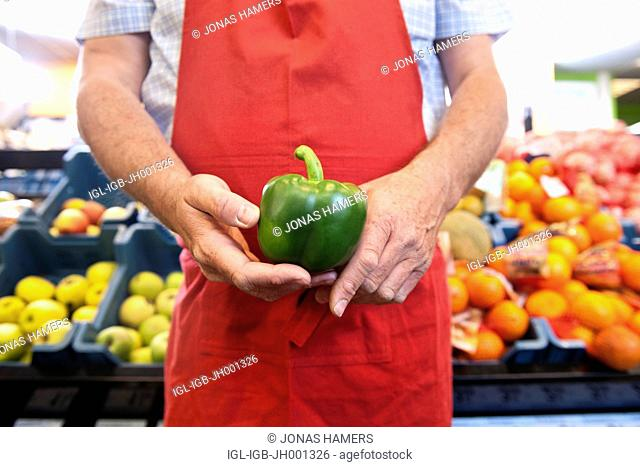Supermarket employee holding goods and food fruit and vegetable