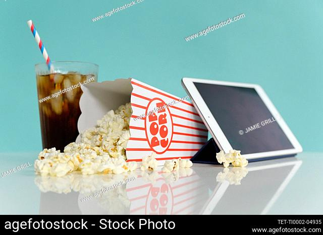 Studio shot of popcorn with digital tablet and soda