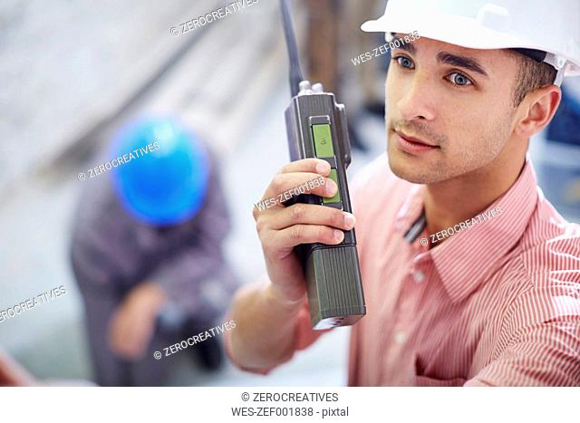 Construction worker talking on two-way radio
