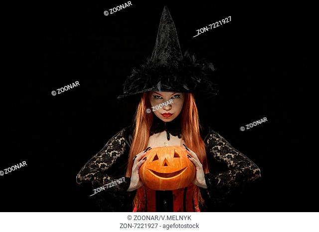 Girl with Halloween pumpkin on black background