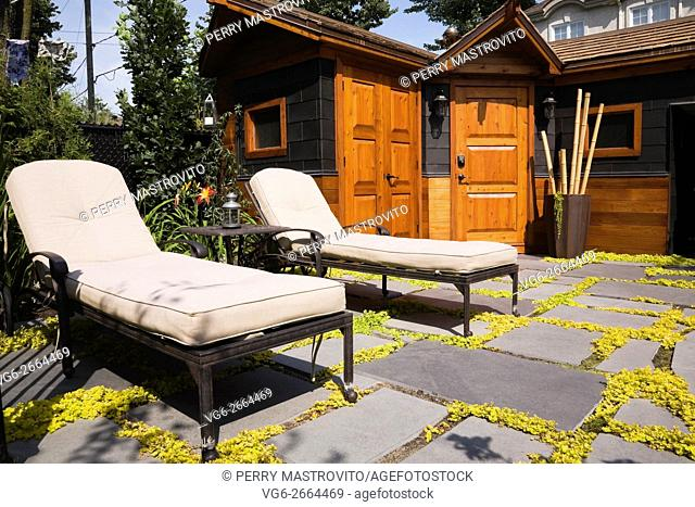 Wooden storage shed and lounge chairs on flagstone patio with yellow Lysimachia nummularia 'Aurea' - Golden Creeping Jenny in landscaped residential backyard in...