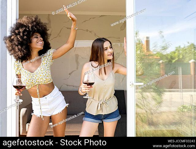 Multi-ethnic female friends with wine glass waving while standing at doorway of house