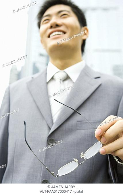 Businessman holding glasses, low angle view