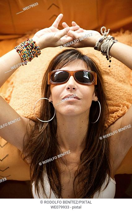 Woman in her late 30s relaxing at home wearing sunglasses