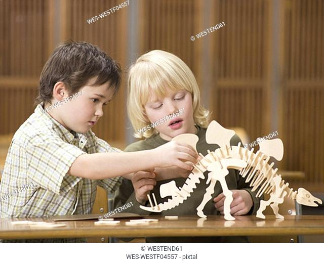 Boys assembling dinosaur skeleton