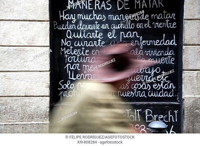 Man with a hat passing by wall with a Bertold Brecht's poem written on, Carrer Tallers, Barcelona. Catalonia, Spain