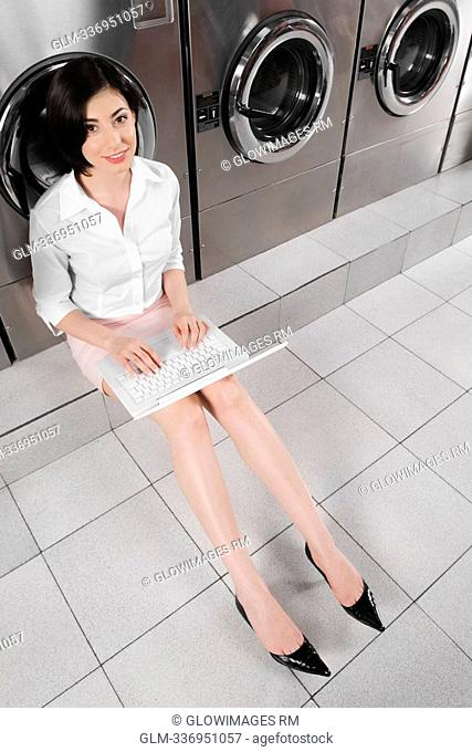 Woman using a laptop in a laundromat