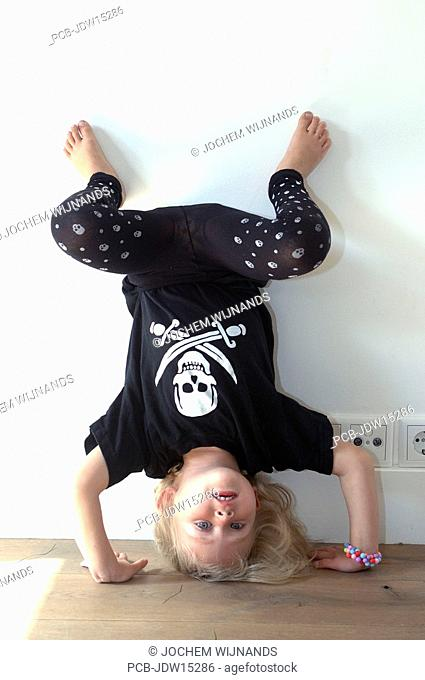 Girl with pirate symbols of skull and crossed swords on her shirt doing a handstand against the wall