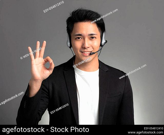 Smiling young asian businessman talking on headset and showing ok sign