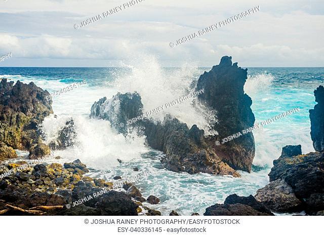 Huge waves crash over lava rocks on the windward shore of the Big Island in Hawaii