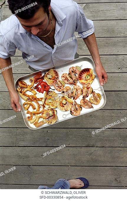 Man carrying a tray of barbecued seafood
