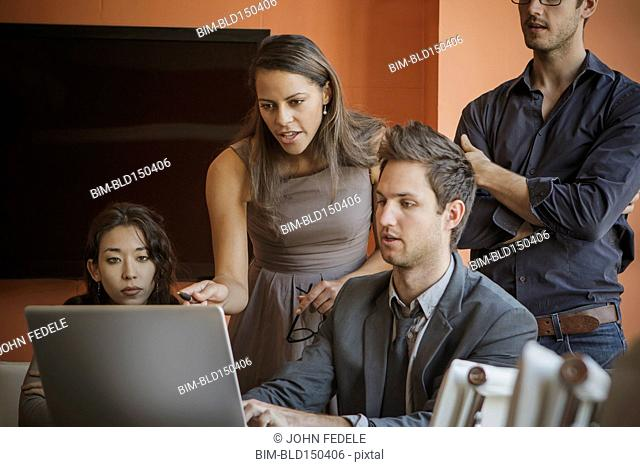 Businesspeople using laptop in meeting