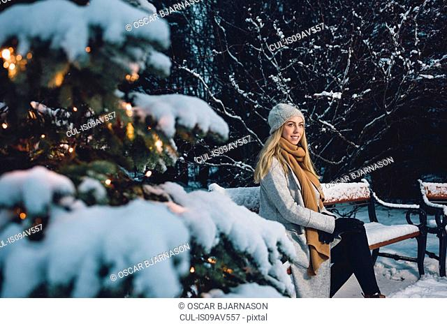 Young woman wearing woollen hat and scarf sitting on snow covered park bench by illuminated christmas tree looking away smiling