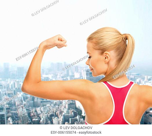 fitness and healthcare concept - young sporty woman showing her biceps