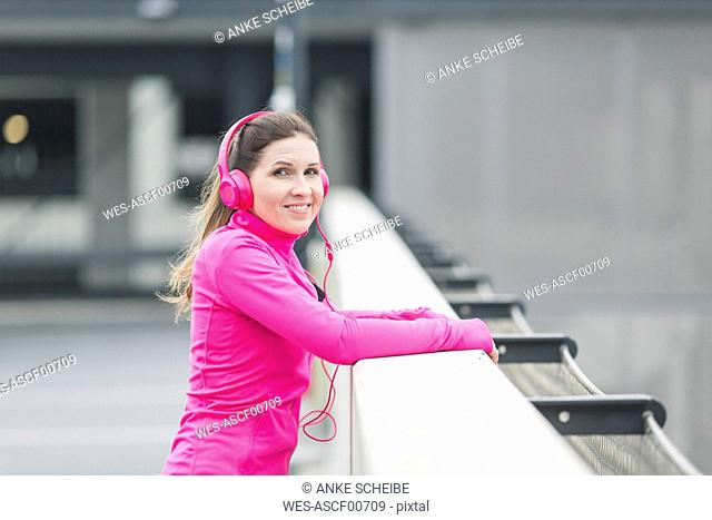 Portait of smiling sportive woman wearing headphones