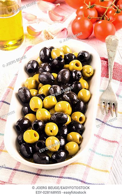 white bowl with oily green and black olives, tomato background, garlic and a bottle of olive oil on a kitchen towel