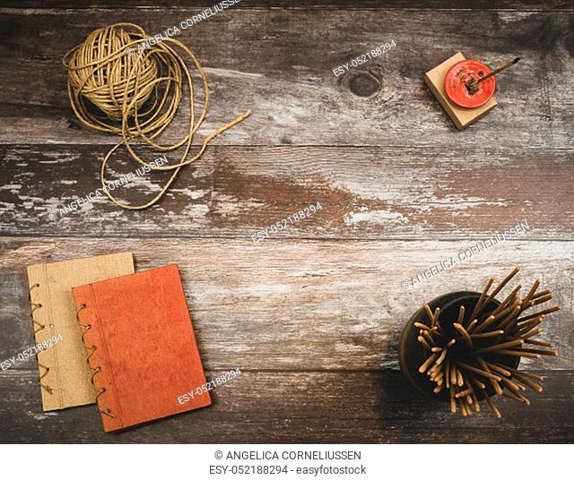 Rustic old vintage wood table with burning incense, incense sticks, natural twine and two small handmade books, with background copyspace - Concept of relaxing...
