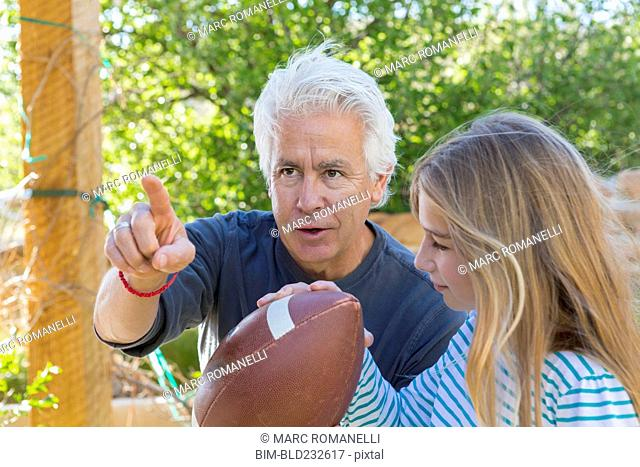 Caucasian grandfather showing granddaughter how to aim football