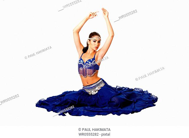 Beautiful Israeli Egyptian Lebanese Middle Eastern belly dancer performer in blue skirt and bra with arms in air sitting, isolated