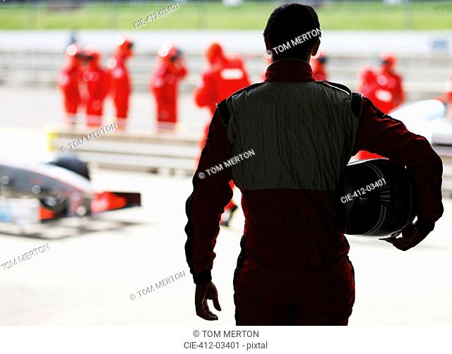 Racer carrying helmet on sidelines