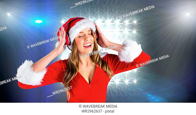 Woman in Santa costume listening to music on headphones