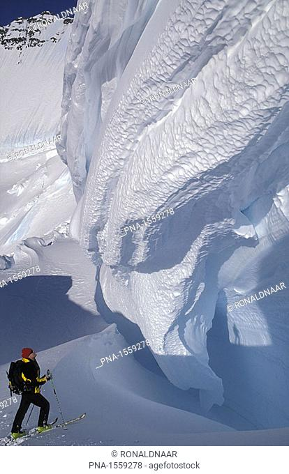 An alpinist on skis crossing a crevasse on the Borgetinde in eastern Greenland