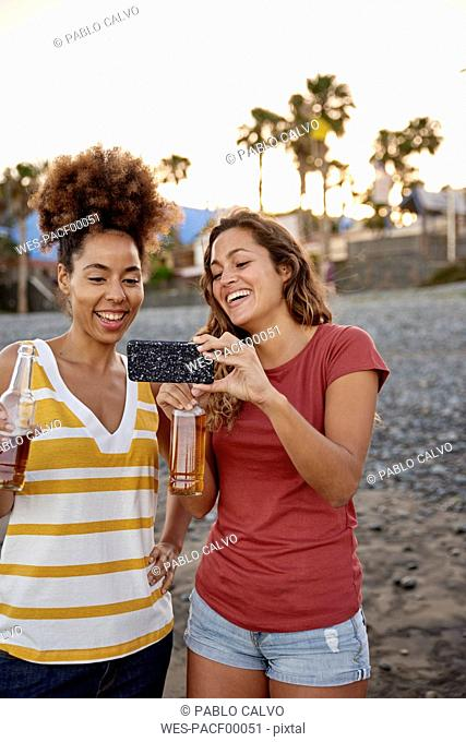 Two laughing friends with beer bottles taking selfie on the beach